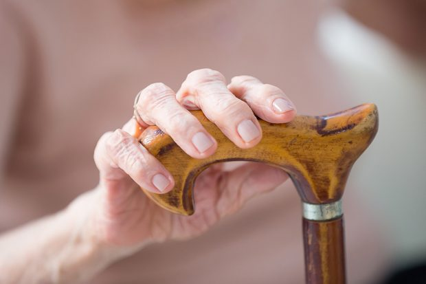 elderly woman holding her walking stick