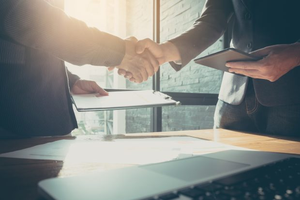Business man and partner shaking hands in office